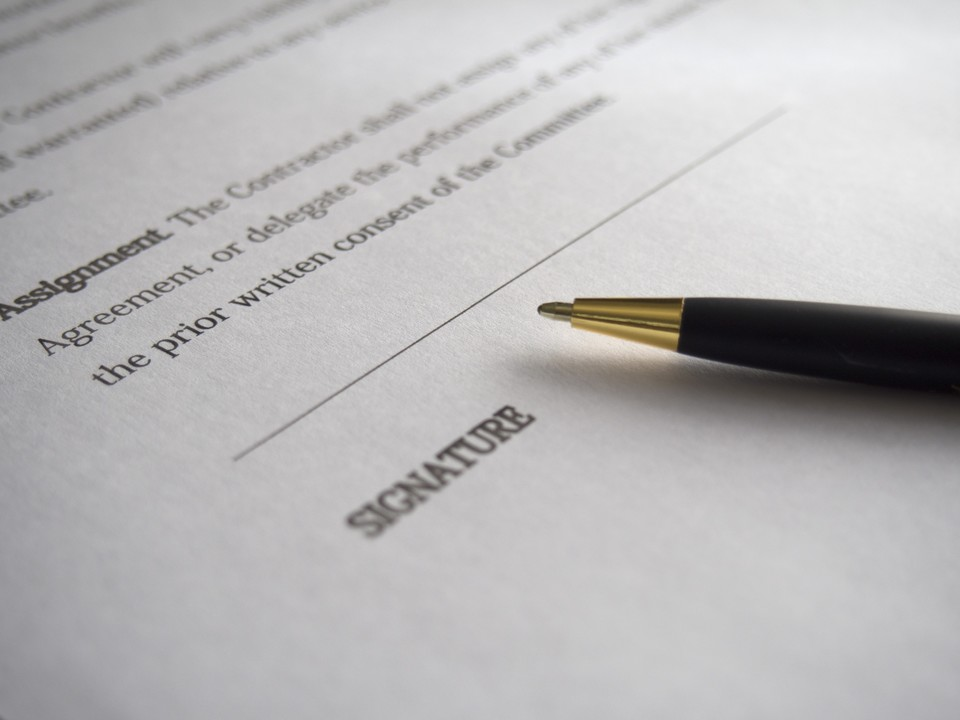 pen on a contract document in a transaction law agreement