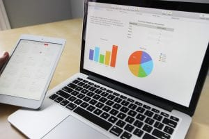 laptop and tablet with graphs outlining potential mistakes hurting the sale of a business