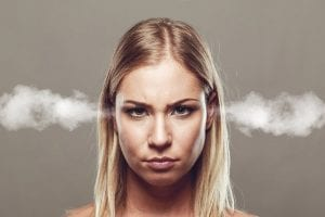 a woman with steam coming out of her eyes, feeling the emotional stress of selling your business