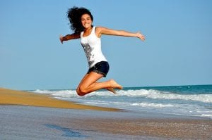 a woman jumping at the beach celebrating selling your business